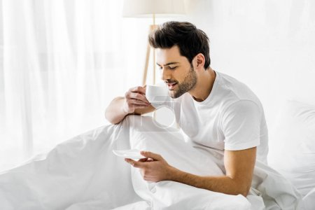 Photo for Smiling man in pajamas drinking coffee in bed in the morning - Royalty Free Image