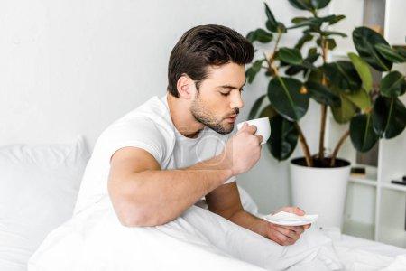 Photo pour Bel homme en pyjama, boire du café au lit le matin - image libre de droit