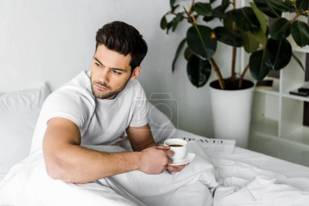 Photo for Thoughtful young man in pajamas holding cup of coffee in bed - Royalty Free Image