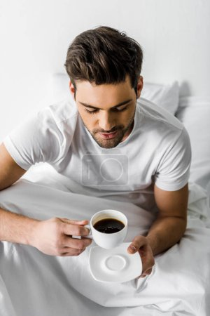 handsome smiling man in pajamas holding cup of coffee in bed