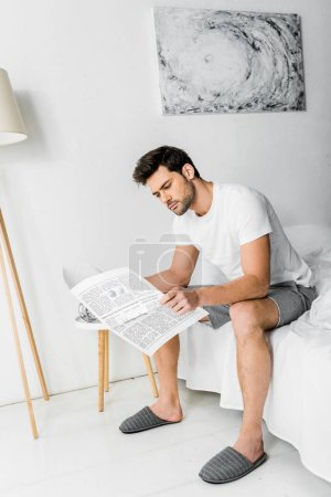 handsome young man in pajamas reading newspaper in bedroom