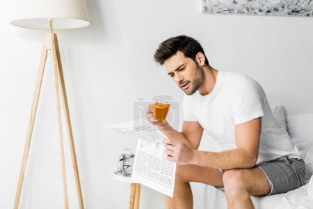 handsome man with cup of tea reading newspaper in bedroom