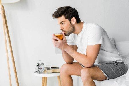 handsome man in pajamas drinking tea in bedroom
