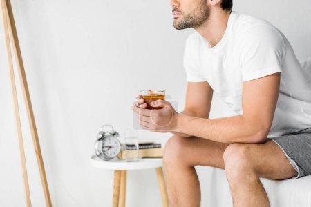 Photo pour Recadrée de l'homme réfléchi tenant la tasse de thé dans la chambre - image libre de droit