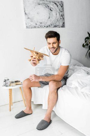 happy man playing with wooden toy plane in bedroom