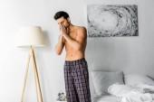 shirtless man with headache standing in bedroom