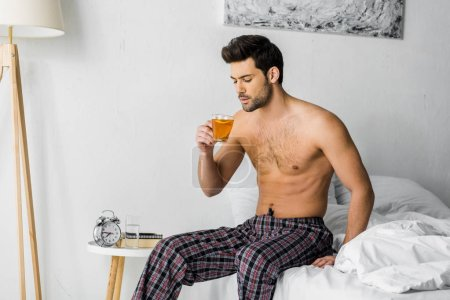 shirtless man holding cup of tea and sitting on bed