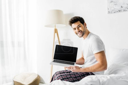 handsome smiling man showing laptop with blank screen