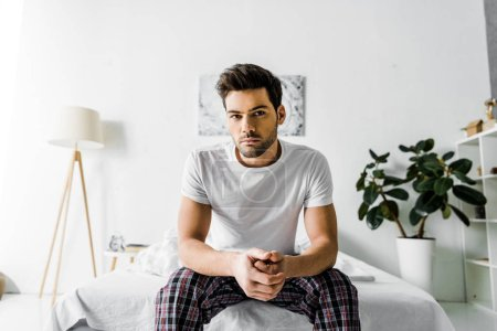 handsome serious man in pajamas sitting on bed at home