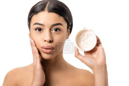 attractive young african american woman holding container with cream and touching face isolated on white
