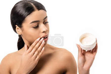 surprised african american girl with hand on face holding container with facial cream isolated on white