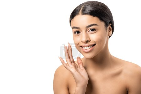 beautiful naked african american girl applying face cream and smiling at camera isolated on white