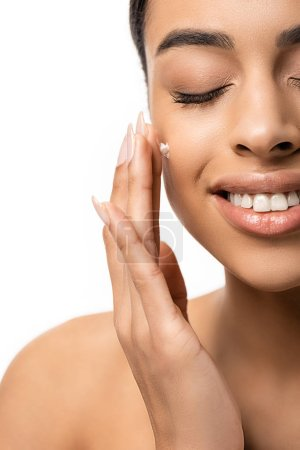 close-up view of happy young african american woman applying face cream isolated on white