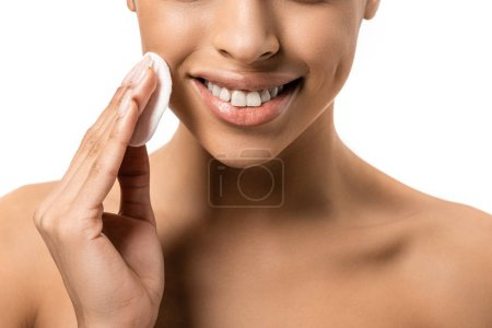 cropped shot of smiling young african american woman cleaning face with cotton disk isolated on white