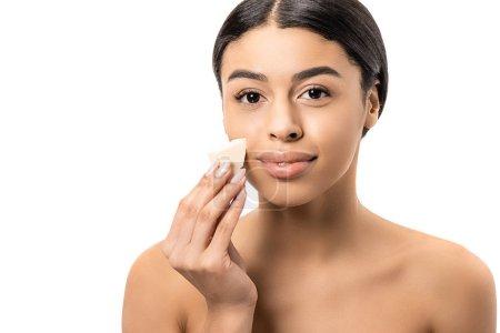Foto de Atractivo joven mujer afroamericana desnuda sosteniendo la esponja de maquillaje y sonriendo a cámara aislada en blanco - Imagen libre de derechos
