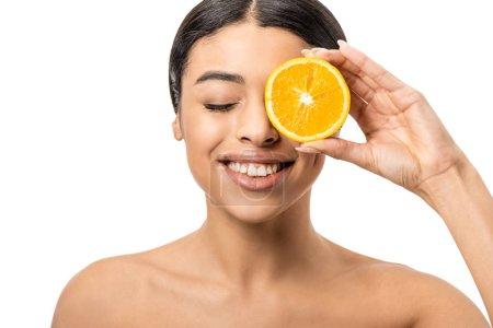 Photo pour Belle fille afro-américaine souriante tenant tranche d'orange près de visage isolé sur blanc - image libre de droit
