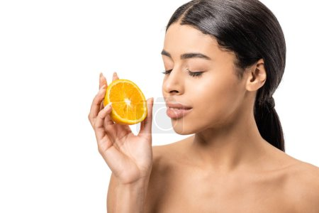 beautiful naked african american woman with closed eyes holding half of orange near face isolated on white