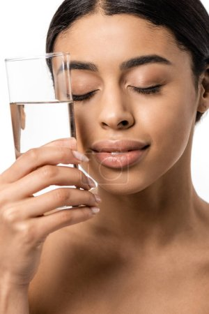 beautiful young african american woman with closed eyes holding glass of clear water near face isolated on white