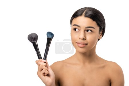 beautiful smiling african american woman holding makeup brushes and looking away isolated on white