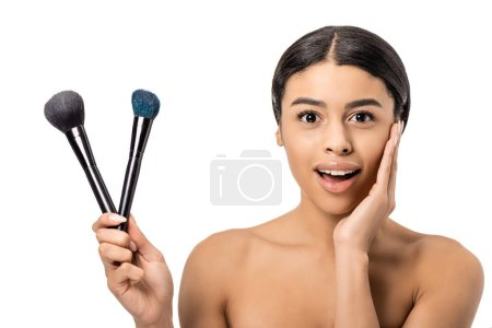 excited naked african american woman holding makeup brushes and smiling at camera isolated on white