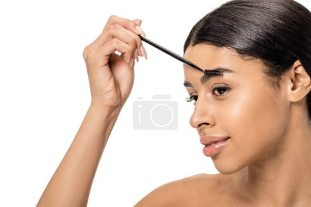 beautiful smiling brunette african american girl correcting eyebrow with brush isolated on white