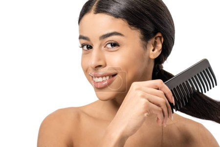 attractive naked young african american woman combing hair and smiling at camera isolated on white