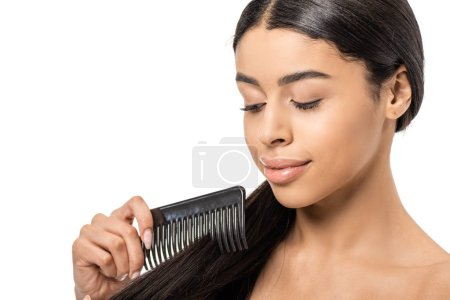 beautiful smiling african american girl combing hair isolated on white