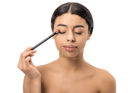 attractive brunette african american girl with closed eyes applying eyeshadow with cosmetic brush isolated on white