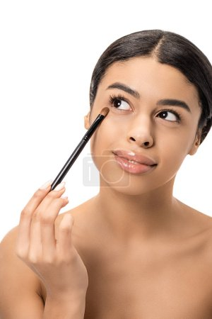 beautiful smiling naked african american woman applying makeup with cosmetic brush and looking away isolated on white
