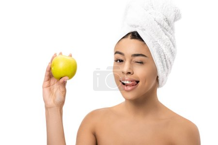happy young african american woman with towel on head holding fresh apple and winking at camera isolated on white