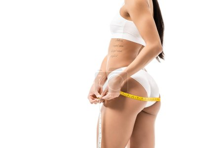 cropped shot of african american girl in underwear measuring hips with tape isolated on white