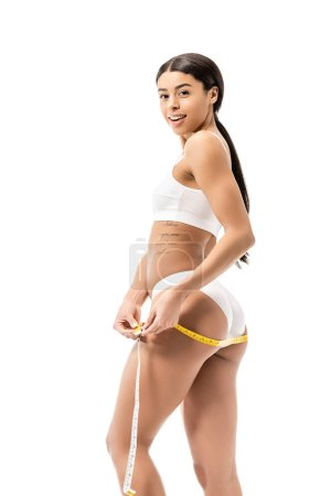 side view of beautiful african american girl in underwear measuring hips with tape and smiling at camera isolated on white