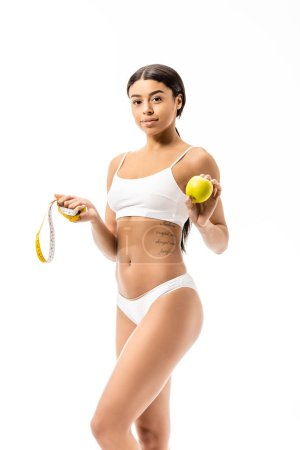 beautiful smiling african american girl in underwear holding apple with measuring tape and looking at camera isolated on white