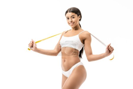 attractive african american girl in underwear holding measuring tape and smiling at camera isolated on white