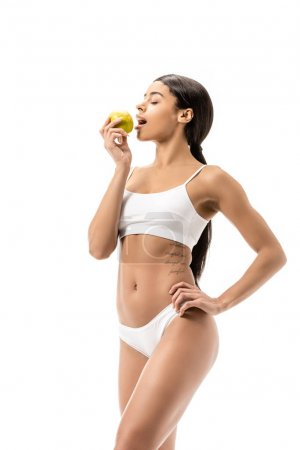 beautiful young african american woman in underwear eating green apple isolated on white