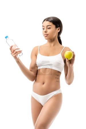 slim young african american woman in underwear holding bottle of water and green apple isolated on white