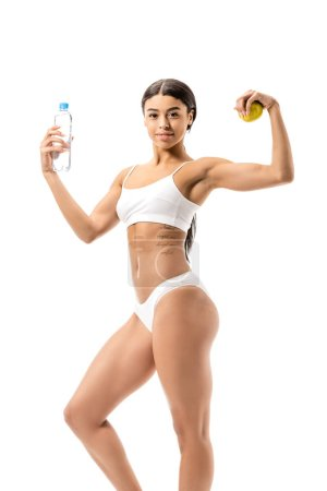 sporty african american girl in underwear holding bottle of water with green apple and showing muscles isolated on white