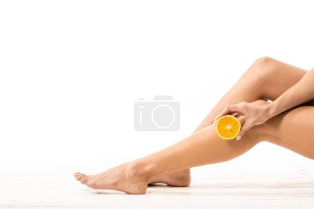 Photo pour Photo recadrée de belles jambes féminines et l'autre moitié d'orange à la main sur blanc - image libre de droit