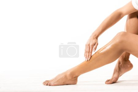 cropped shot of african american woman doing sugar wax epilation on white