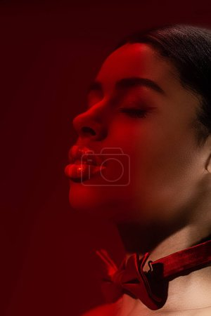 toned image on young seductive african american woman with closed eyes and red bow tie isolated on burgundy