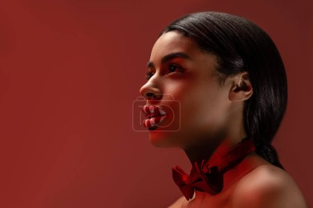 side view of beautiful naked african american girl with bow tie and striped lips looking away isolated on burgundy