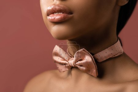 cropped shot of sensual african american girl with pink bow tie isolated on burgundy