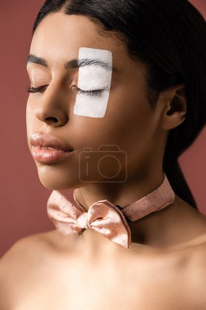 beautiful young african american woman with bow tie and white paint on face posing with closed eyes isolated on brown