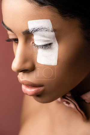 attractive african american girl with white paint stroke on eye looking down isolated on brown