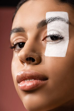 close-up view of attractive african american girl with white paint stroke on eye looking at camera isolated on brown