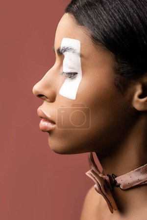 side view of beautiful african american woman with white paint stroke on eye and bow tie isolated on brown
