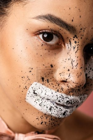 close-up view of beautiful african american woman with bow tie and paint on face looking at camera isolated on pink