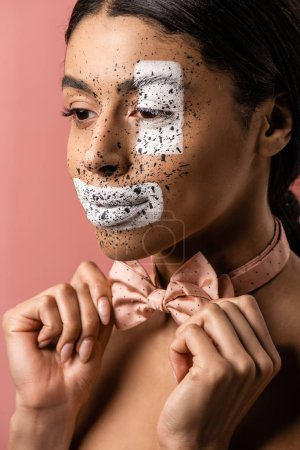 beautiful african american woman with paint on face adjusting bow tie and looking away isolated on pink