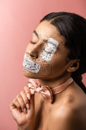 beautiful sensual african american woman with paint on face and closed eyes adjusting bow tie isolated on pink