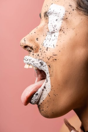 side view of african american girl with paint splashes on face showing tongue out isolated on pink